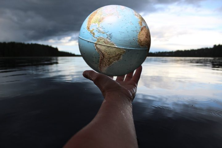 A hand holding a globe illustrating the Surprises of the Spirit retreat at Spirit in the Desert